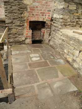 Flagstones on the floor of a stone building, with a fireplace set into an area of bricks at the back