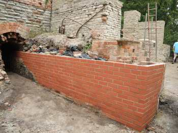 Rebuilt brick wall in front of stone wall